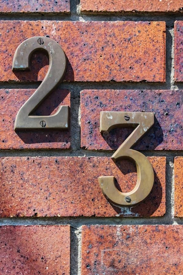 Close-up van grungy nummer 23 op verontruste baksteen wordt geschroeft die stock fotografie