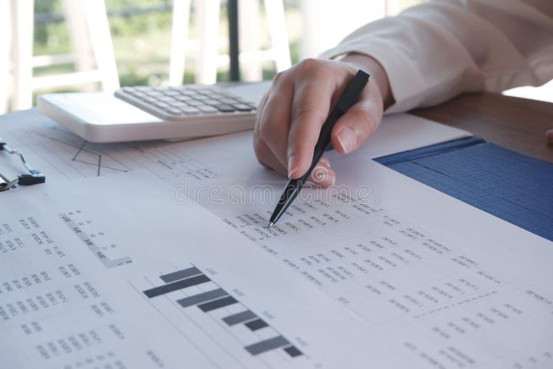 close-up van hand die in bureau, bestuderend gebruikend calculator en schrijvend iets met documenten en grafiek aan lijst werken stock foto