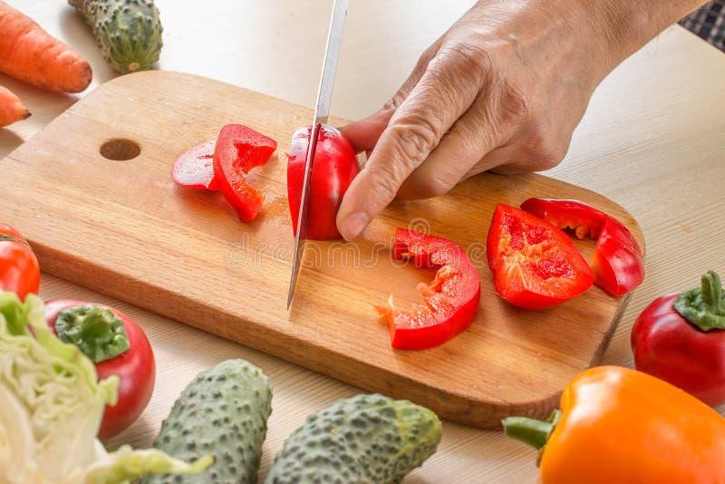 Close-up van handen van de scherpe groenten van de chef-kokkok royalty-vrije stock foto