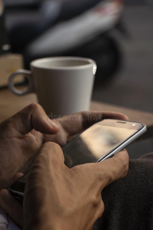 Close-up van handen die mobiel in een koffie gebruiken stock afbeeldingen