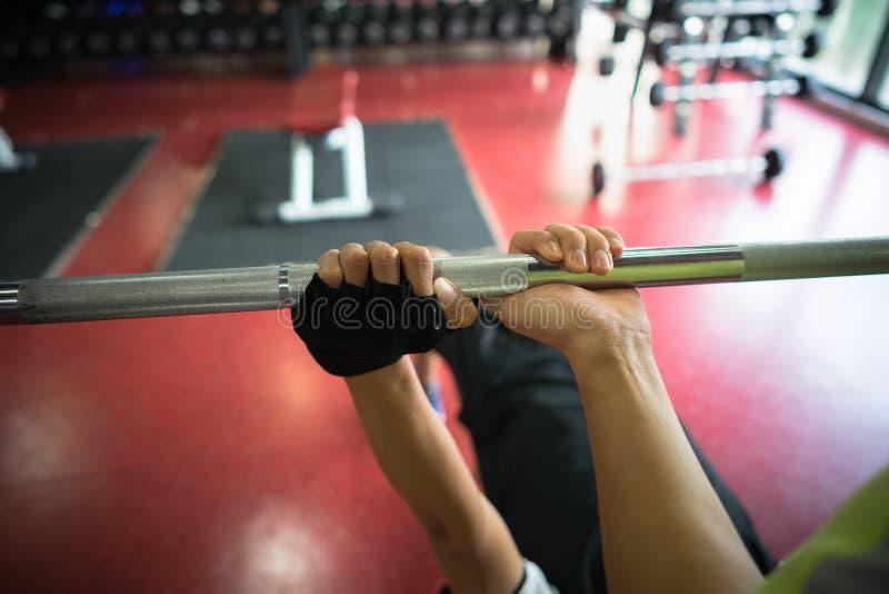 Close-up van handen van jonge mens opleiding met geschiktheidsinstructeur die barbell in gymnastiek gebruiken royalty-vrije stock afbeelding