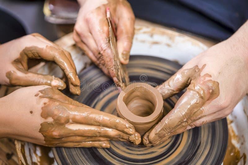 Close-up van Handen van Professionele Mannelijke Pottenbakker die Zijn Vrouwelijke Leerling onderwijzen royalty-vrije stock fotografie