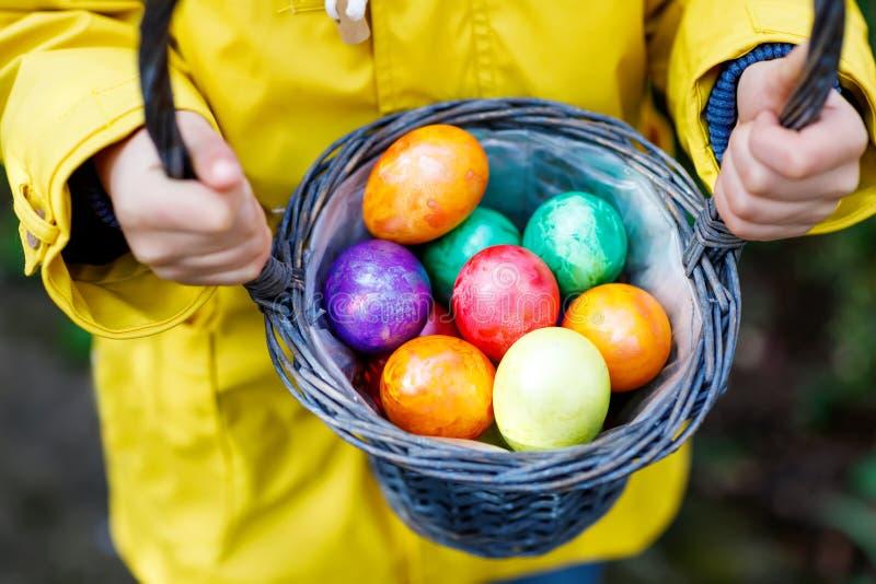 Close-up van handen van weinig kind met kleurrijke paaseieren in mand stock fotografie