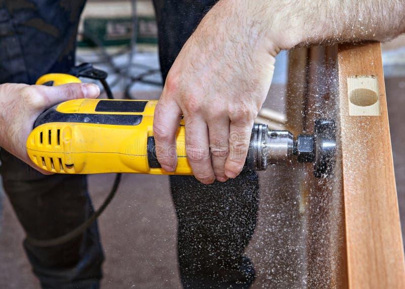 Close-up van handentimmerman met het gele slot van het boor geboorde gat stock afbeeldingen