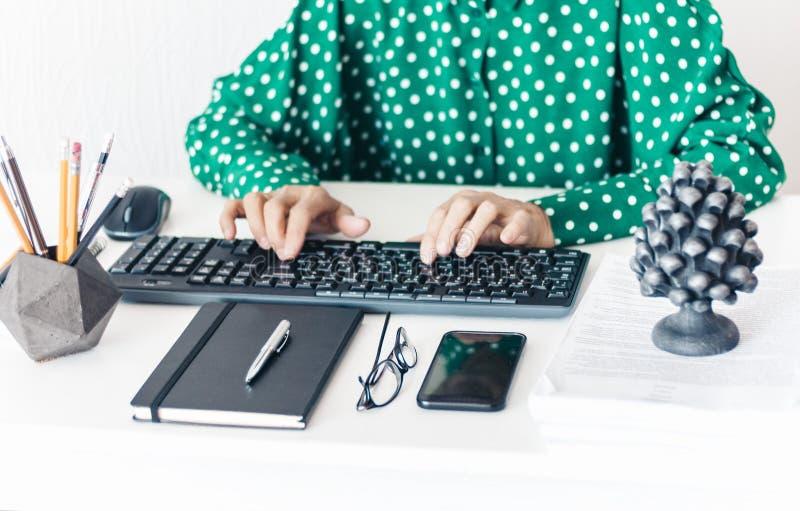 Close-up van handenvrouw op middelbare leeftijd in het groene blouse typen op toetsenbordlaptop computer, concrete houder met pot royalty-vrije stock foto
