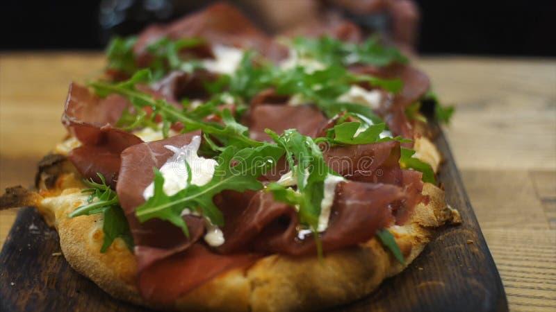Close-up van heerlijke Italiaanse kleine pizza met salade, bacon en roomkaas die op een houten schop boven de lijst leggen stock foto's