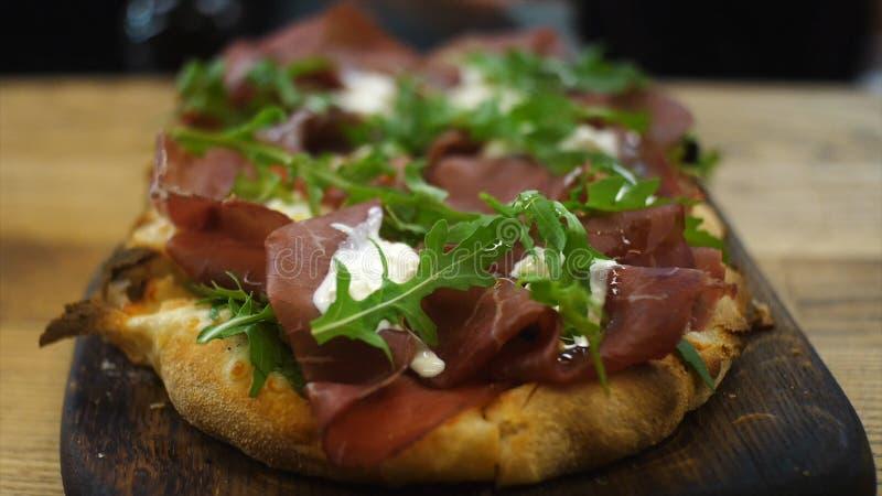 Close-up van heerlijke Italiaanse kleine pizza met salade, bacon en roomkaas die op een houten schop boven de lijst leggen royalty-vrije stock foto