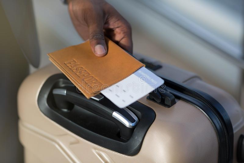 Close-up van het Afrikaans man paspoort van de handholding, bagage en vliegtuigkaartje stock fotografie