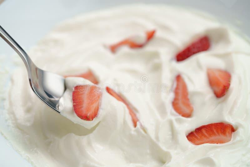 Close-up van het eten met lepel organische gesneden aardbeien in slagroom royalty-vrije stock fotografie