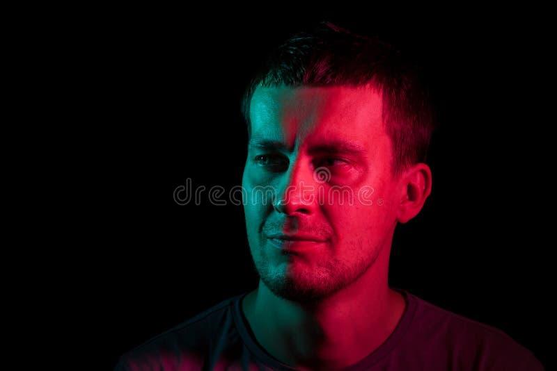 Close-up van het gezicht van een ongeschoren hoofd van een Kaukasische mens die weg met stoppelveld in dark kijken die, aan één k stock afbeelding