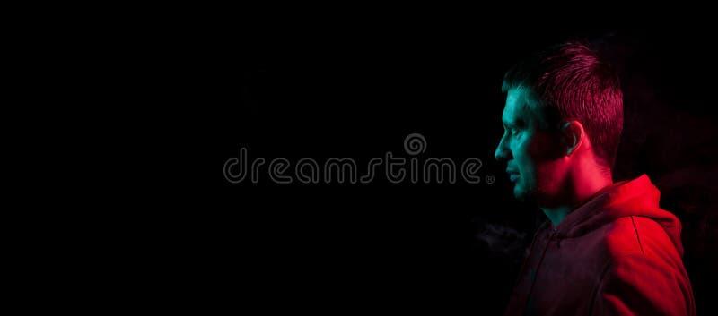 Close-up van het gezicht van een ongeschoren gezicht van een Kaukasische mens die weg met stoppelveld in dark kijken die, aan één stock foto's