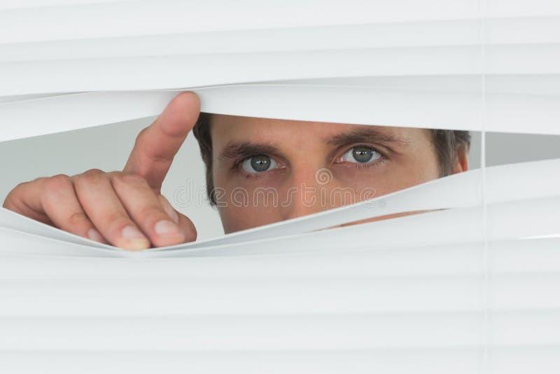 Close-up van het groene eyed zakenman gluren door zonneblinden royalty-vrije stock fotografie
