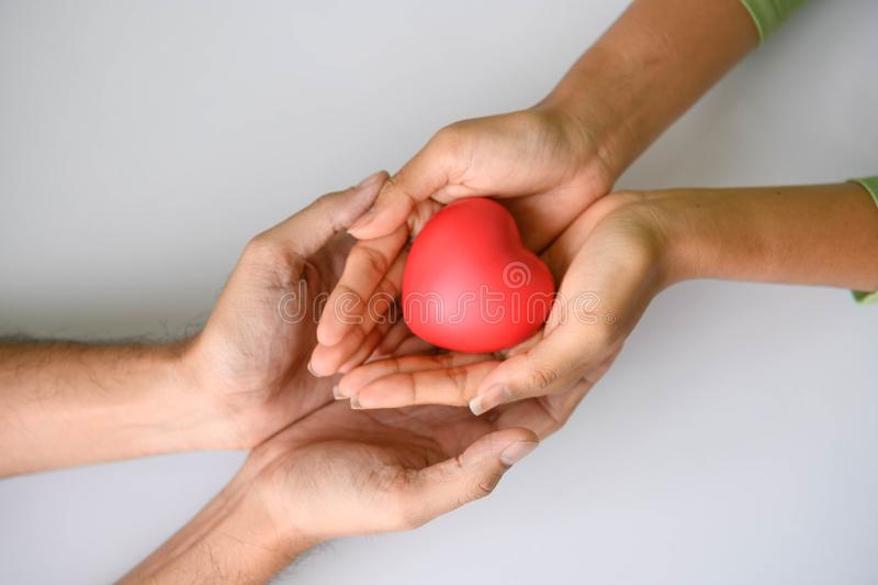Close-up van het Helpen van hand van hartdonor voor patiënt in hartkwaal De man geeft rood hart aan vrouw als paar Mensenlevensst stock afbeeldingen