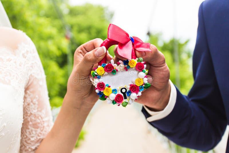 Close-up van het huwelijks de bloemenslot in handenbruid en stock afbeeldingen
