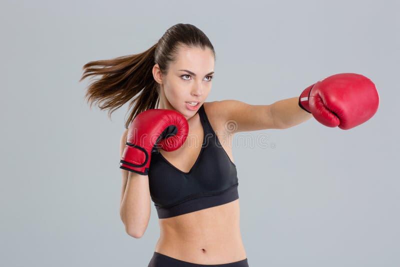 Close-up van het jonge geschiktheidsvrouw in dozen doen gebruikend rode handschoenen stock afbeelding