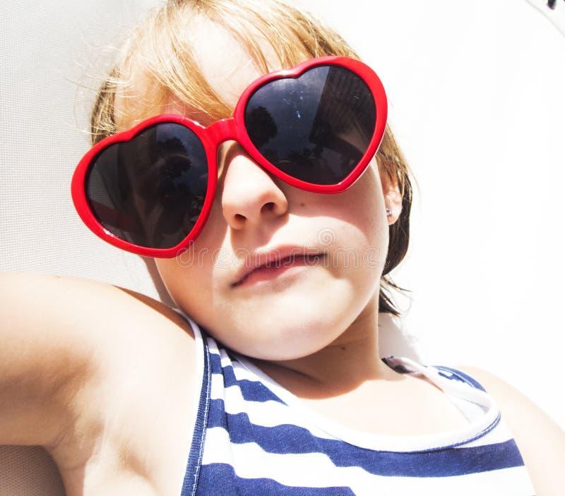 Close-up van het jonge Kaukasische meisje zonnebaden met sunglassses stock afbeelding