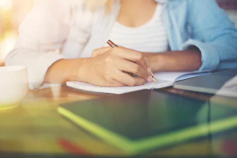 Close-up van het jonge mooie schrijven en het werk van vrouwenhanden met l stock foto