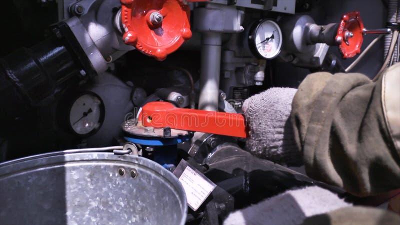 Close-up van het materiaal van de brandvrachtwagen scène De brandweerman draait rode kleppen op brandvrachtwagen Concept brand royalty-vrije stock foto