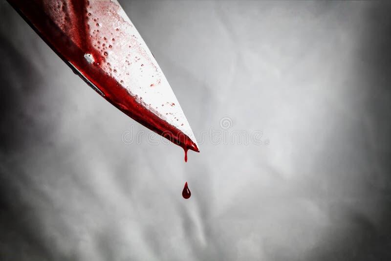 close-up van het mes van de mensenholding met bloed wordt gesmeerd dat en nog dripp stock afbeelding