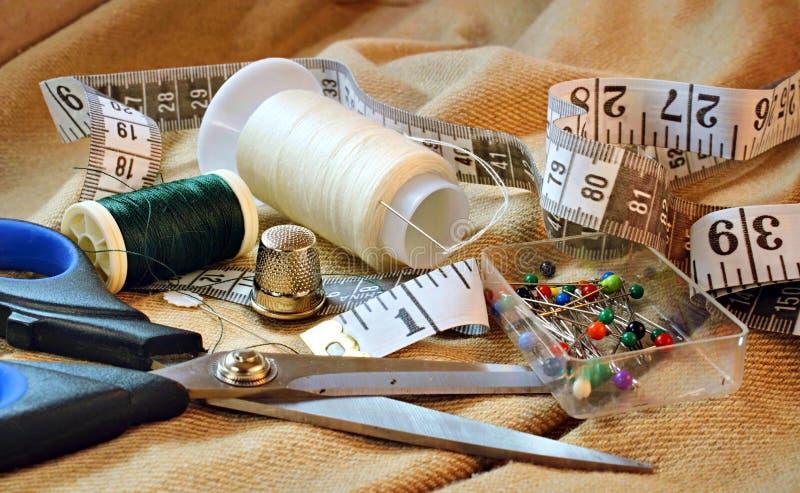 Close-up van het naaien van uitrusting op stoffenachtergrond met inbegrip van schaar, draadspoelen, die band, vingerhoedje en spe stock fotografie