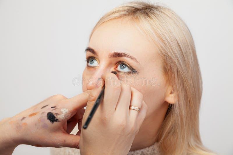 Close-up van het toepassen van samenstelling in de salon op het model met geopende ogen in de oosterse stijl, de kunstenaar die g stock fotografie