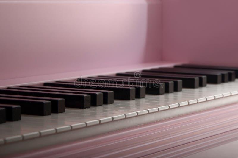 Close-up van het toetsenbord van een roze piano Reeks witte en zwarte knopen stock afbeelding