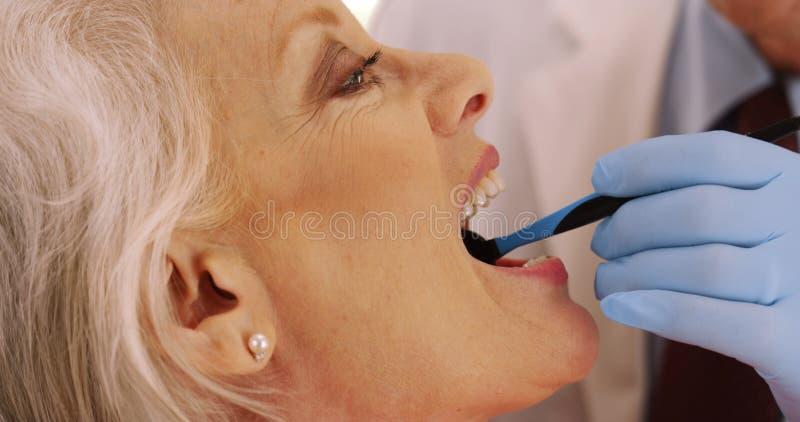 Close-up van hogere tandarts die bejaarde` s tanden in het bureau onderzoeken royalty-vrije stock fotografie