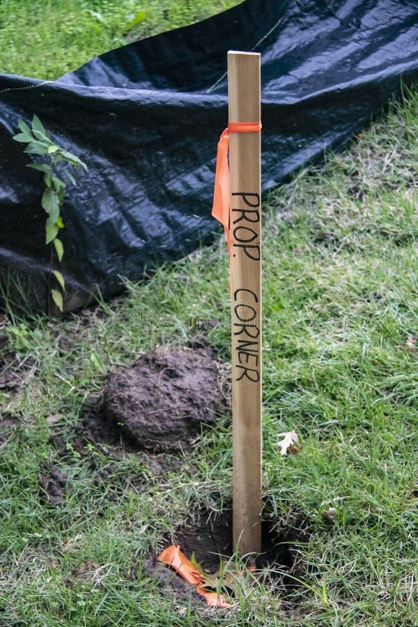 Close-up van houten staak in grond met oranje band en Bezitshoek duidelijk die op het dichtbij bouwbarrière van zware zwarte word stock foto's