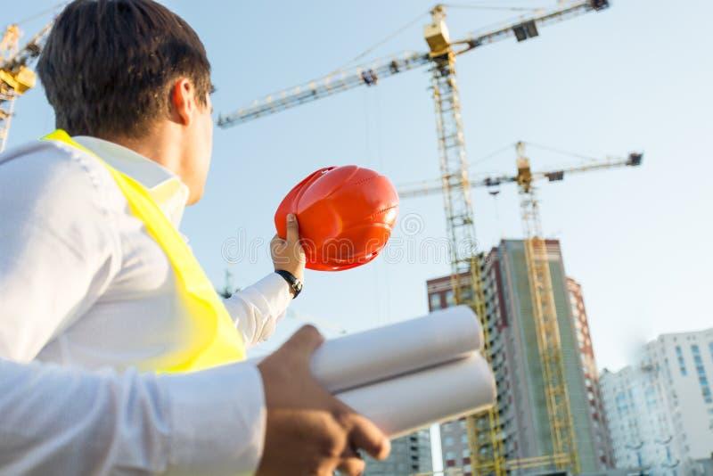 Close-up van ingenieur het stellen op bouwterrein met oranje bouwvakker stock afbeeldingen