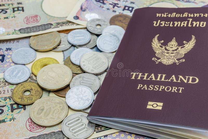 Close-up van Japanse Yenbankbiljetten en Japans Yenmuntstuk met het paspoort van Thailand financieel geld en reisconcept royalty-vrije stock afbeelding