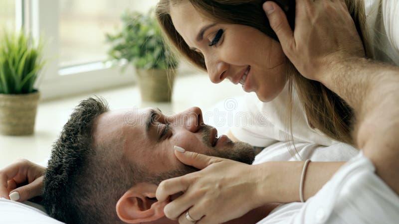 Close-up van jong mooi en het houden van paarspel en kus in bed bij de ochtend Aantrekkelijke mens die en van hem kussen koestere royalty-vrije stock foto