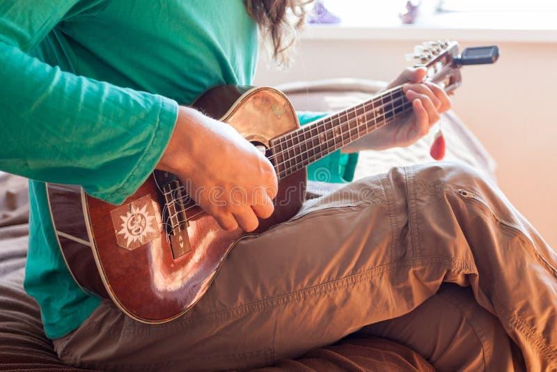Close-up van jonge mensen` s handen die een akoestische gitaarukelele spelen bij het huis De ukelele van de mensenholding stock afbeelding