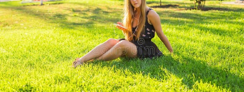 Close-up van jonge mooie vrouw die van muziek in openlucht op een gras genieten royalty-vrije stock afbeelding