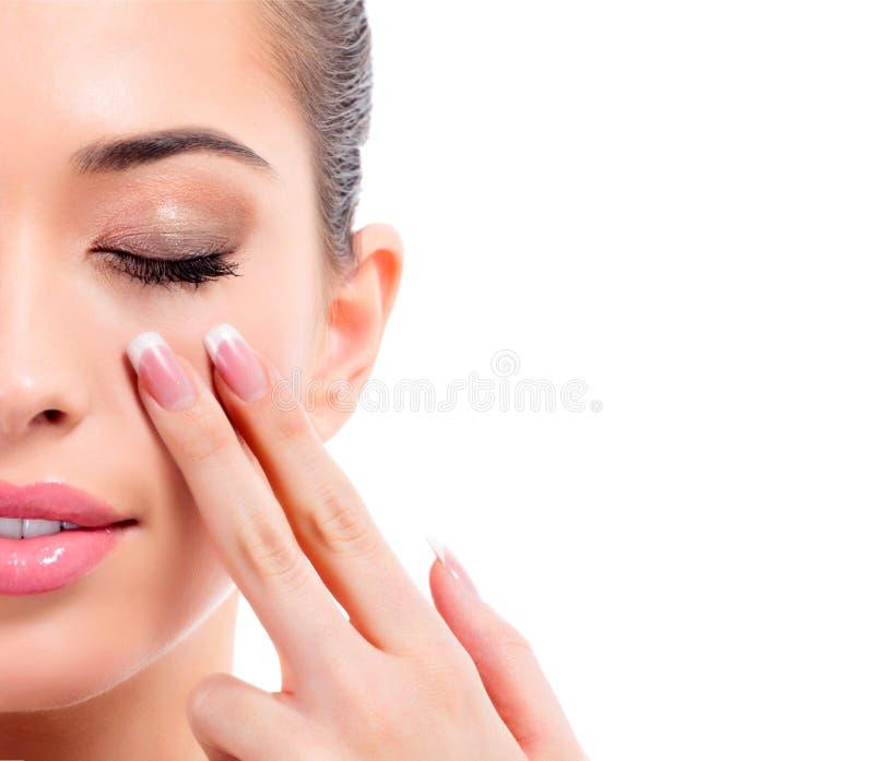 Close-up van jonge schoonheidsvrouw wordt geschoten die haar gezicht masseren dat royalty-vrije stock afbeeldingen