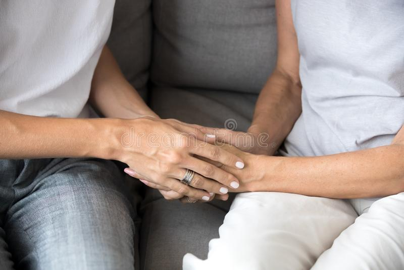 Close-up van jonge vrouw die oude vrouwelijke handen houden die steun geven stock afbeelding
