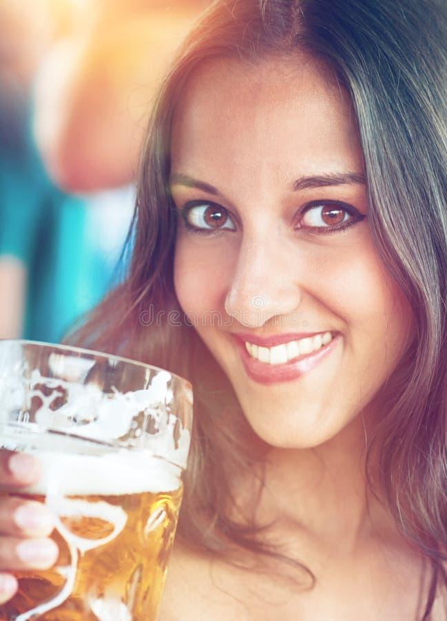 Close-up van jonge vrouw met een glas bier stock foto's