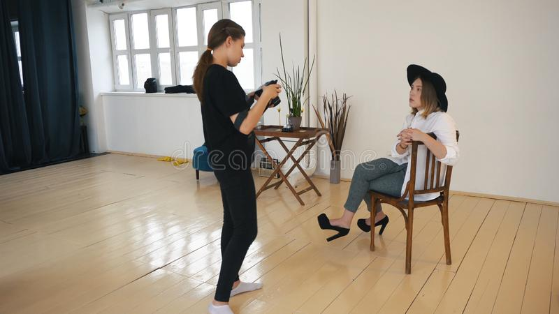 Close-up van jonge vrouwelijke fotograaf in zwarte kleren die foto's tonen aan modieus jong model in zwarte hoed, wit overhemd royalty-vrije stock afbeelding