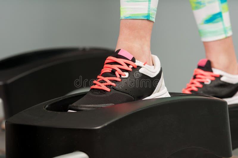 Close-up van jonge vrouwelijke voeten die aan stepper werken stock foto