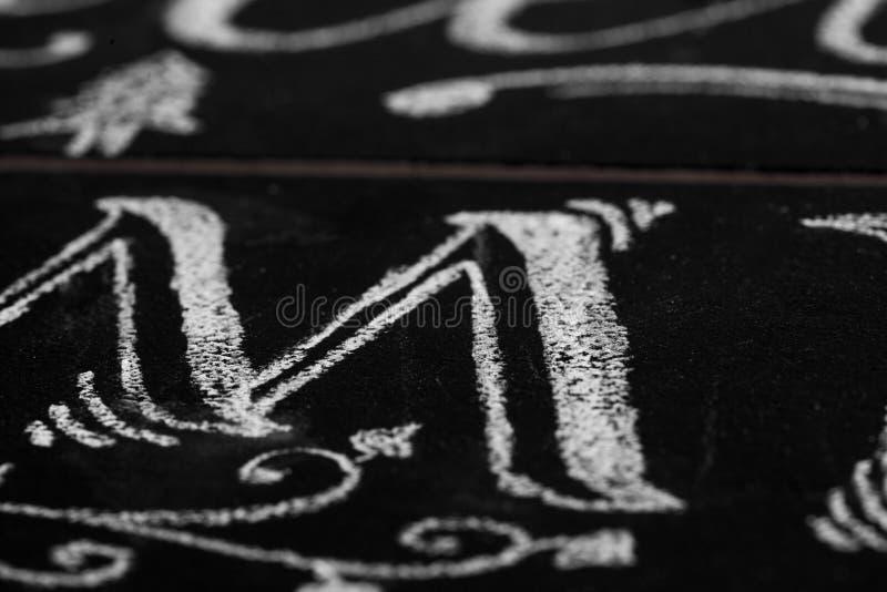 Close-up van kalligrafiebrief M met krijt wordt getrokken dat Ondiepe diepte stock foto