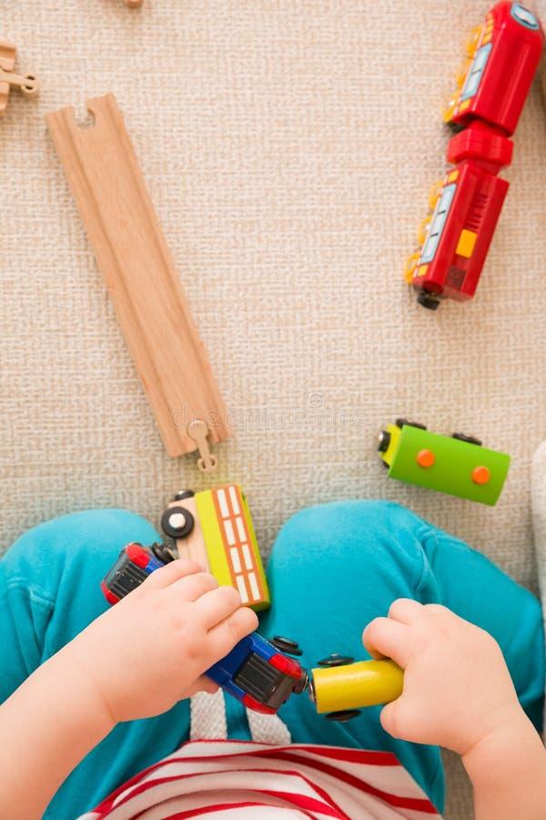Close-up van kind` s handen die met houten treinspeelgoed en spoorweg spelen Hoogste mening De zitting van de peuterjongen en het stock fotografie