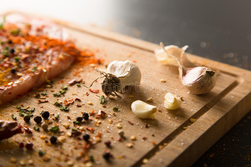 Close-up van knoflook met ruwe verse varkensvleesvlees en kruiden stock afbeeldingen