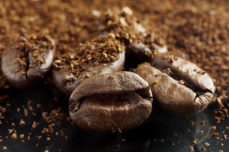 Close-up van koffiepoeder en bonen wordt geschoten op zwarte die stock fotografie
