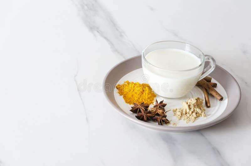 Close-up van kop melk en verschillende kruiden op de plaat Concept voorbereiding van smakelijke kurkuma latte royalty-vrije stock foto