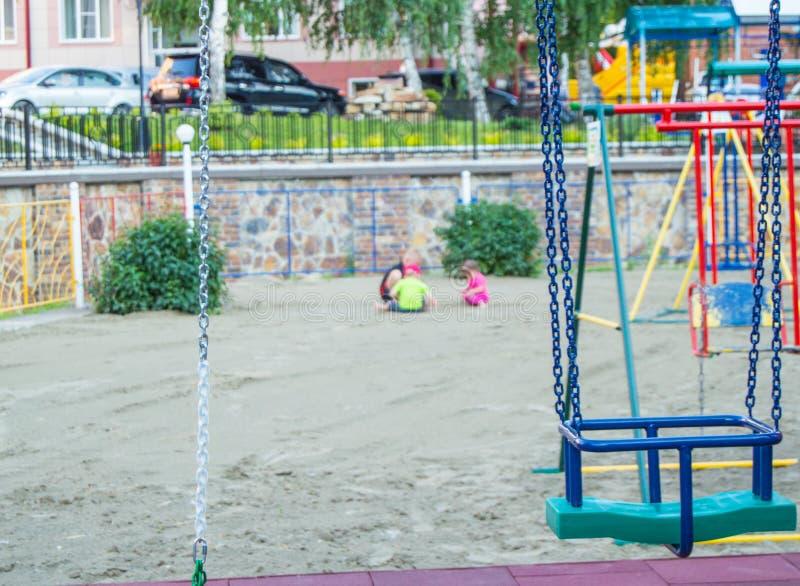 Close-up van lege kleurrijke plastic babyschommeling op Speelplaats in Park op de zomerdag royalty-vrije stock fotografie