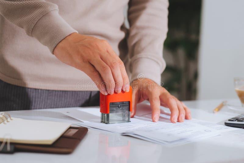 Close-up van mannelijk hand het stempelen document op houten bureau royalty-vrije stock foto's