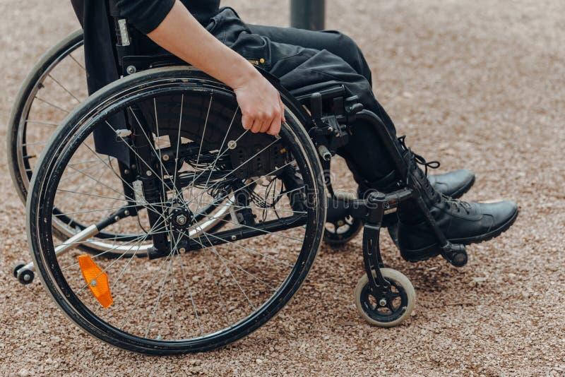 Close-up van mannelijke hand op wiel van rolstoel tijdens gang in park stock afbeeldingen