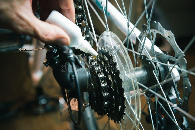 Close-up van mannelijke handen die en een een fietsketting en toestel met olienevel schoonmaken oli?en Het werk proces stock fotografie