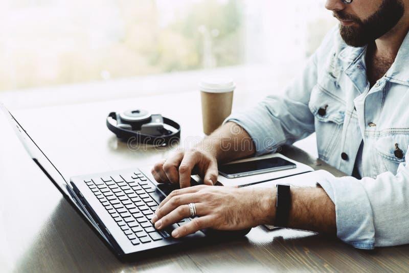 Close-up van mannelijke handen die op computertoetsenbord typen De gebaarde mens gebruikt laptop in koffie Zakenman die ver werke royalty-vrije stock afbeeldingen