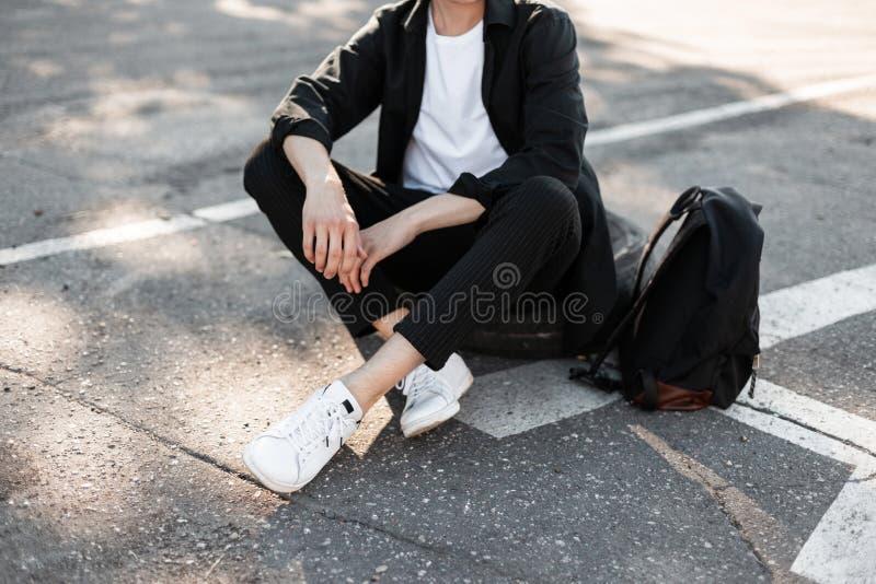 Close-up van mannelijke modieuze benen Jonge maniermens in elegant zwart overhemd in gestreepte uitstekende broeken in witte tenn royalty-vrije stock foto