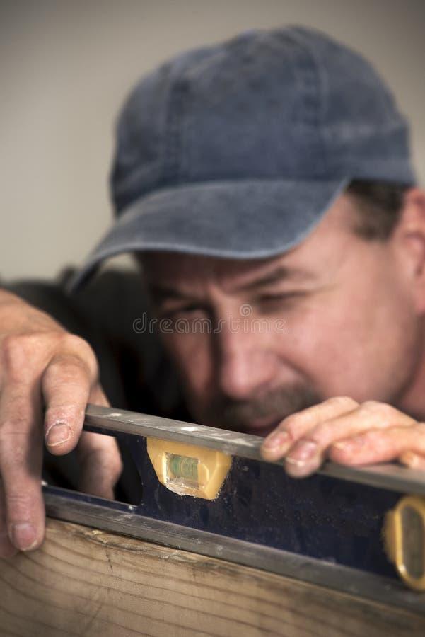 Close-up van mannelijke timmerman die niveauhulpmiddel bekijken op houten raad royalty-vrije stock afbeelding